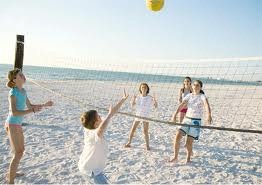 Children playing volleyball on the beach